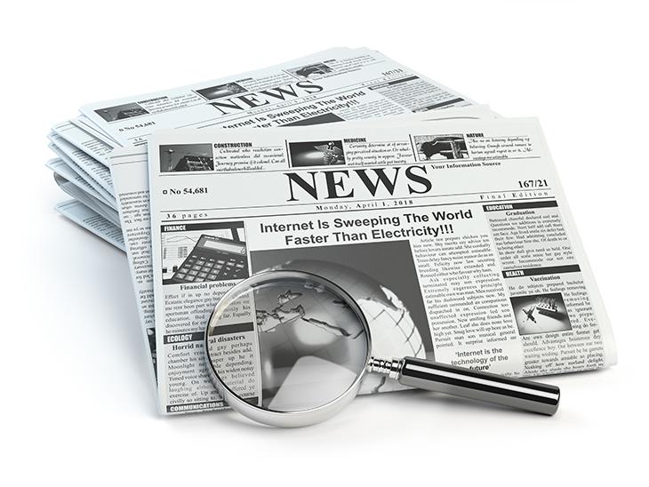 新聞と虫眼鏡の画像